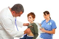 Medico maschio ed infermiera femminile che esaminano un ragazzo Fotografie Stock