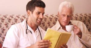 Medico maschio ed uomo senior che leggono un libro archivi video