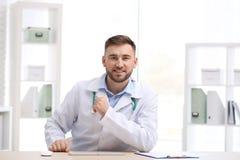 Medico maschio facendo uso di video chiacchierata nel luogo di lavoro, vista dalla macchina fotografica fotografia stock libera da diritti