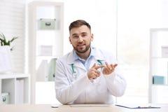 Medico maschio facendo uso di video chiacchierata nel luogo di lavoro immagine stock libera da diritti