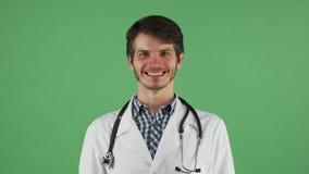 Medico maschio felice che sorride alla macchina fotografica sul chromakey fotografia stock libera da diritti