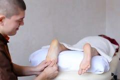 Medico maschio massaggia i piedi della ragazza che si trova sullo strato in bri Immagine Stock Libera da Diritti
