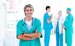 Medico maschio maturo che si leva in piedi con la sua squadra Immagini Stock Libere da Diritti