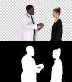 Medico maschio offre il farmaco alla giovane donna, Alpha Channel fotografie stock libere da diritti