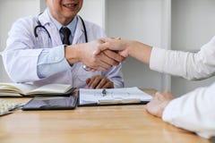Medico maschio professionista in camice che stringe la mano con il paziente femminile dopo riuscito raccomanda i metodi di tratta immagine stock