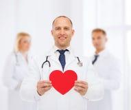 Medico maschio sorridente con cuore e lo stetoscopio rossi Fotografia Stock