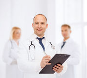 Medico maschio sorridente con la lavagna per appunti e lo stetoscopio Immagini Stock Libere da Diritti