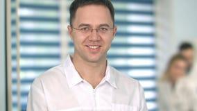 Medico maschio in vetri che sorride alla macchina fotografica mentre personale medico che lavora ai precedenti Fotografie Stock