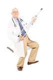 Medico maturo che gioca chitarra su una gruccia Fotografia Stock