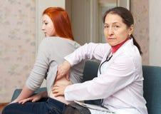 Medico maturo che tocca dietro del paziente immagine stock