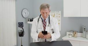 Medico maturo che utilizza smartphone nell'ufficio immagine stock libera da diritti