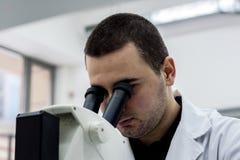 Medico medico o scientifico femminile dell'uomo del ricercatore che guarda throu Fotografia Stock Libera da Diritti