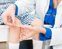 Medico mette la fasciatura adesiva Fotografia Stock