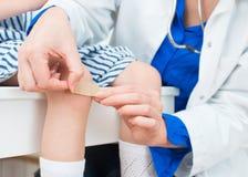 Medico mette la fasciatura adesiva Fotografia Stock Libera da Diritti