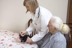 Medico mette lo stabilizzatore sul polso della donna anziana fotografia stock libera da diritti