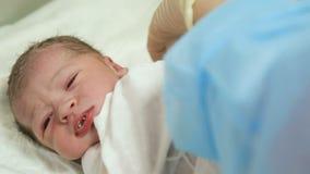 Medico mette un neonato con un morsetto sul cordone ombelicale stock footage