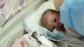 Medico mette un neonato con un morsetto sul cordone ombelicale archivi video