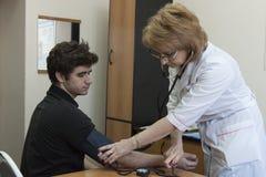 Medico misura la pressione al paziente fotografia stock libera da diritti
