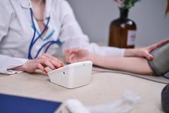 Medico misura la pressione nell'ufficio Fotografia Stock Libera da Diritti