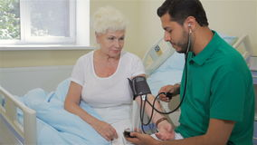 Medico misura la pressione sanguigna della donna senior video d archivio