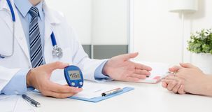 Medico mostra il glucometer con il livello del glucosio fotografie stock