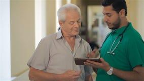Medico mostra qualcosa sulla sua compressa all'uomo senior archivi video
