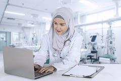 Medico musulmano grazioso lavora con il computer portatile Fotografie Stock Libere da Diritti