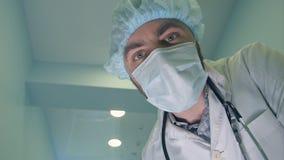 Medico nella maschera che esamina giù il paziente che controlla la sua coscienza immagine stock libera da diritti