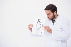 Medico nella prova dell'occhio di rappresentazione del cappotto del laboratorio immagine stock