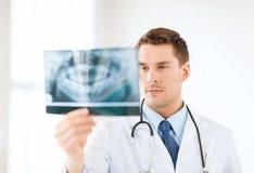 Medico o dentista maschio interessato che esamina raggi x Fotografia Stock