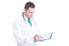 Medico o erba medica maschio che analizza i grafici sulla lavagna per appunti Fotografie Stock