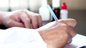 Medico o farmacista che si siede alla tavola e che scrive prescrizione sulla forma di RX archivi video