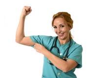 Medico o infermiere di emergenza di md della donna che posa sorridere allegro con lo stetoscopio che mostra il bicipite fotografia stock