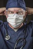 Medico o infermiere di sguardo risoluto con usura protettiva e Stet Fotografia Stock