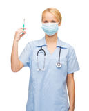 Medico o infermiere femminile in siringa della tenuta della maschera Fotografia Stock