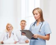 Medico o infermiere femminile sorridente con la lavagna per appunti Fotografia Stock Libera da Diritti