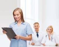 Medico o infermiere femminile sorridente con la lavagna per appunti Fotografie Stock Libere da Diritti