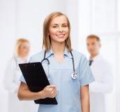Medico o infermiere femminile sorridente con la lavagna per appunti Immagine Stock