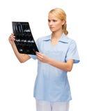 Medico o infermiere serio che esamina raggi x Fotografia Stock