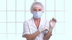 Medico o l'infermiere femminile invecchiato mezzo mette sopra i guanti video d archivio