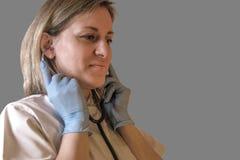 Medico o l'infermiere femminile mette in stetoscopio in orecchie La donna indossa i guanti uniformi e blu del lattice La ragazza  fotografie stock libere da diritti