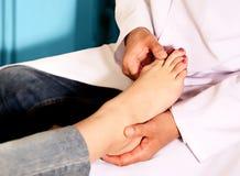 Medico ortopedico nel suo ufficio con il modello dei piedi Fotografia Stock Libera da Diritti