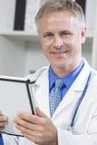 Medico ospedaliero maschio che per mezzo del calcolatore del ridurre in pani Fotografie Stock Libere da Diritti