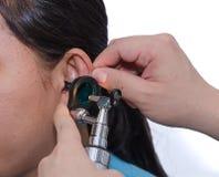 Medico OTORINOLARINGOIATRICO che controlla l'orecchio del paziente facendo uso dell'otoscopio con un inst Fotografia Stock Libera da Diritti
