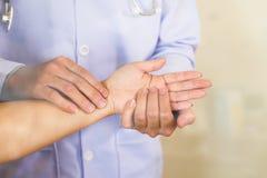 Medico passa l'impulso di sensibilità sul polso femminile Immagine Stock Libera da Diritti