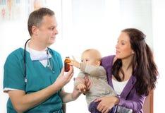Medico pediatrico che dà la bottiglia di pillole alla madre con il bambino Fotografie Stock Libere da Diritti