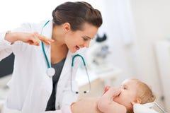 Medico pediatrico che gioca con il bambino sull'indagine Fotografie Stock Libere da Diritti