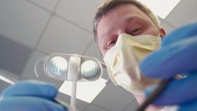 Medico piacevole sta curando il paziente nell'ufficio dentario e poi sta mostrando il pollice video d archivio