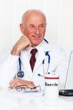 Medico in pratica con lo stetoscopio ed il computer portatile. Fotografia Stock