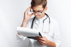 Medico premuroso, esaminando i documenti e fa le note nei documenti, un giovane studente con una cartella in sue mani, su un wh Fotografia Stock